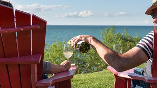man pouring chardonnay in wine glass by a lake